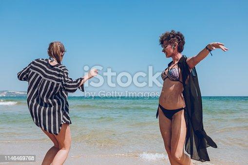 Two young, beautiful, attractive, happy women dancing on the beach, Albena, Bulgaria.