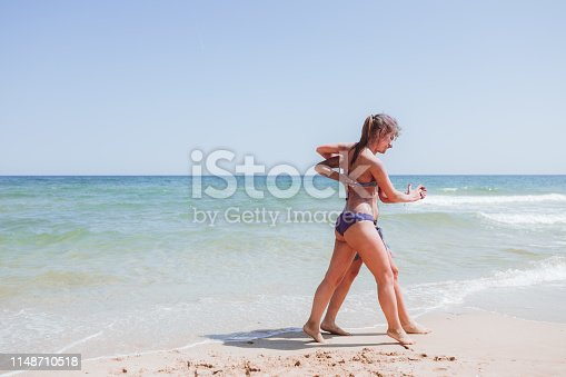 Young, playful girlfriends dancing on the beach of Albena, Bulgaria with sea and clear sky as background.