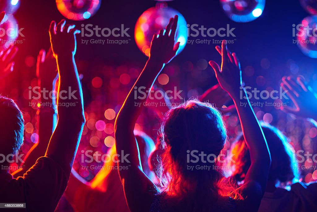 Dancing party Group of young people with raised arms dancing in night club 2015 Stock Photo