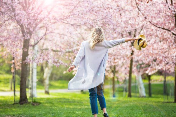Dancing, running and whirling in beautiful park with cherry trees in bloom Young woman enjoying the nature in spring. Dancing, running and whirling in beautiful park with cherry trees in bloom. Happiness concept springtime stock pictures, royalty-free photos & images