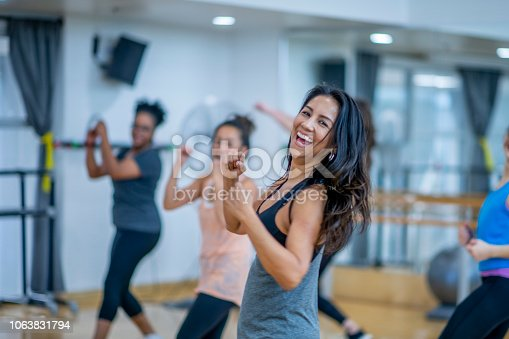 A beautiful woman looks into the camera laughing while she dances in this fitness class. She is surrounded by her friends who are doing the same.