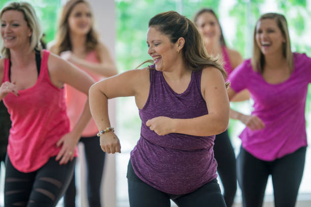 Dancing Together in a Fitness Class A group of women are working out at the gym and are taking an aerobic dance fitness class. exercise class stock pictures, royalty-free photos & images