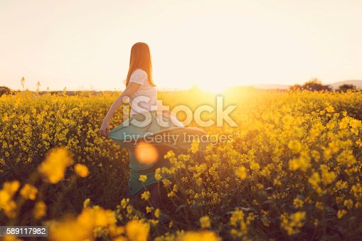 Rear view of a beautiful, russet young woman dancing in the middle of the flower meadow, surrounded by yellow flowers