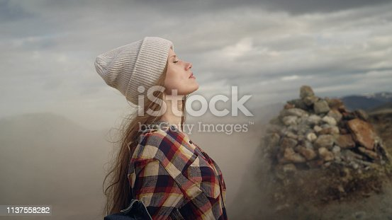 Young woman dancing on a geothermal area. Enjoying steam. Geysers in background
