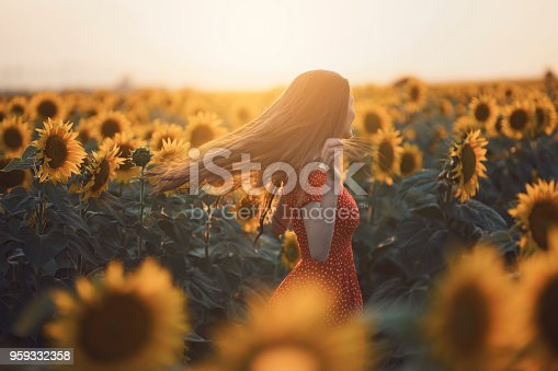 Beautiful, young woman in red dress dancing and enjoying in the sunflower field.