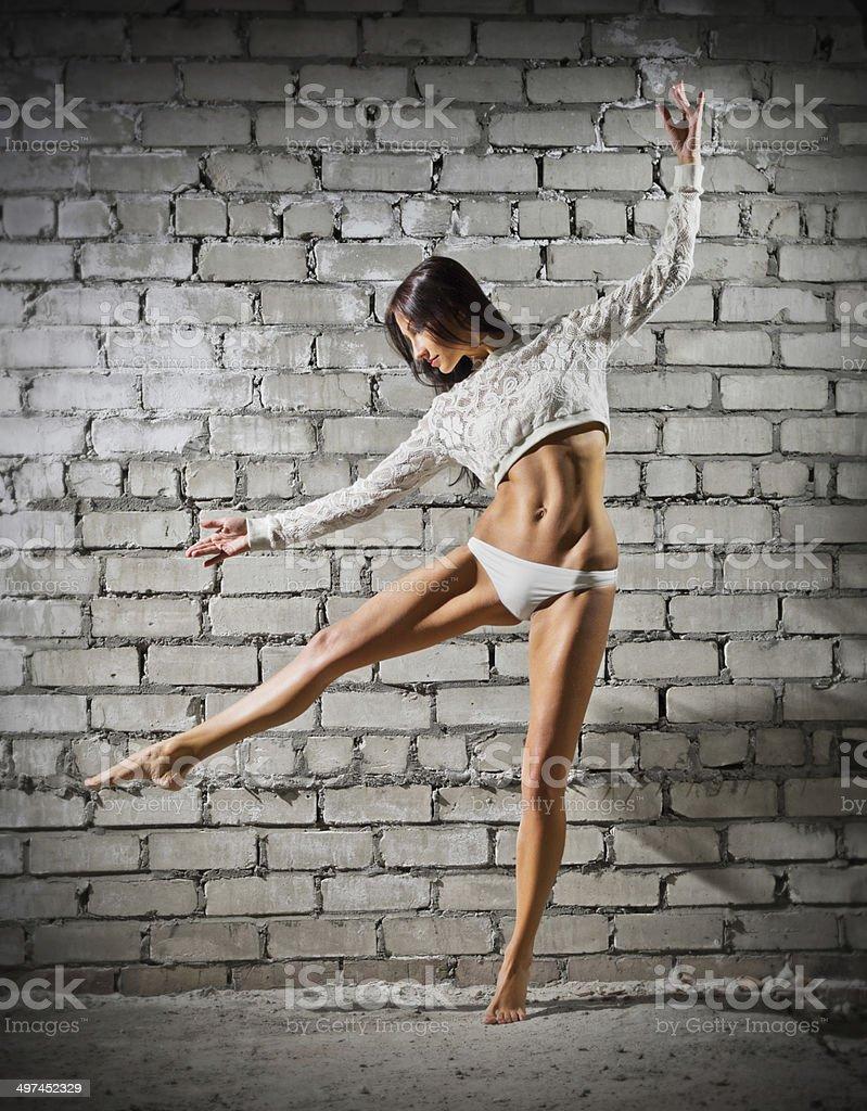Dancing woman on grey wall (normal version) stock photo
