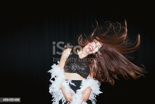 Young excited Asian woman dancing in nightclub