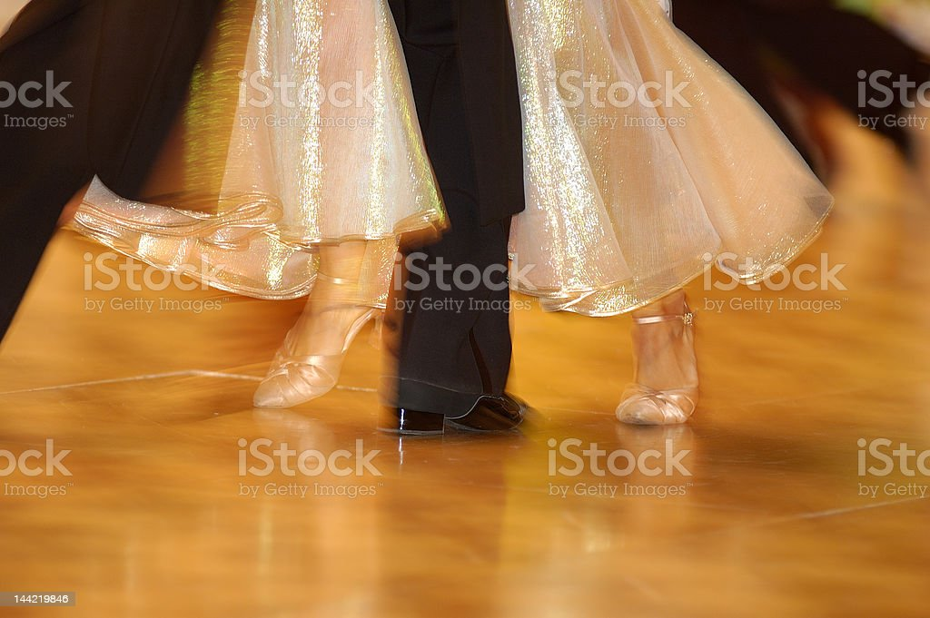 Dancing woman's feet on orange floor with man's foot inbetween stock photo