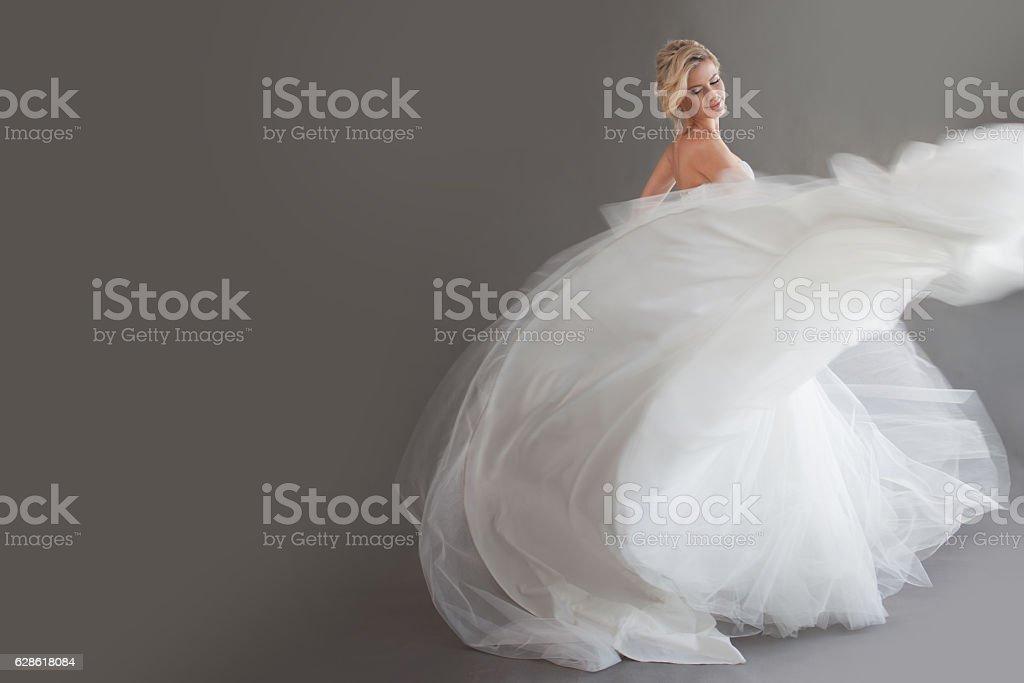 Dancing young bride in luxurious wedding dress. Pretty girl in - foto de stock