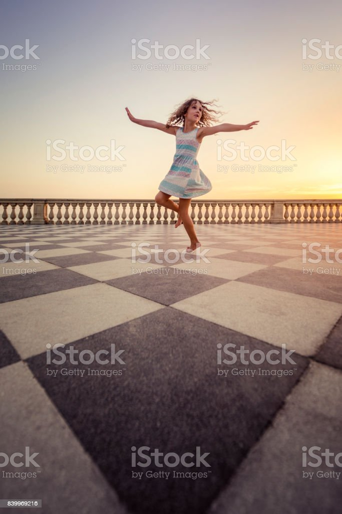 Dancing young girl at Sea promenade in Livorno Tuscany stock photo