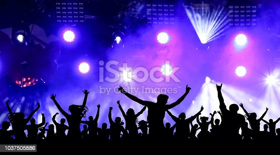 istock Dancing youth party, illustration. Crowd of cheerful people at a concert. Silhouettes of a crowd of fans in front of bright scene lights 1037505886