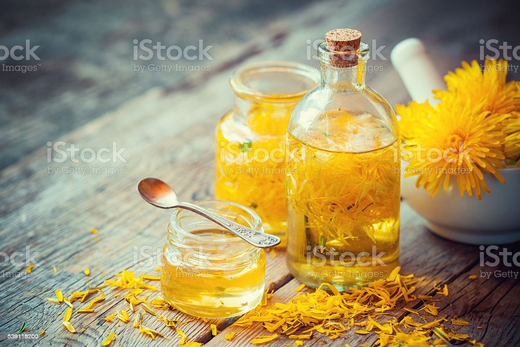 Dandelion tincture or oil bottles, mortar and honey on table. stock photo