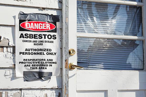 Segnale di pericolo di amianto vicino a casa, porta d'ingresso - foto stock