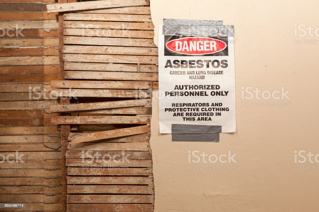 A Danger Asbestos Warning Sign Hangs Next to Exposed Broken Wood Wall stock photo
