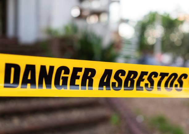 Danger Asbestos warning tape barrier stock photo