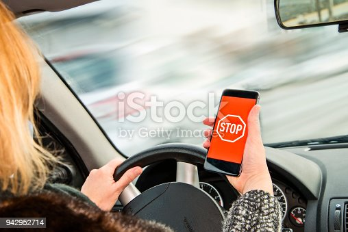 Woman holds a smartphone with stop sign in her hand while driving