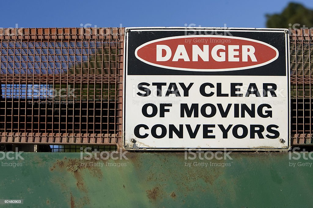 Danger conveyor sign on side of a machine royalty-free stock photo