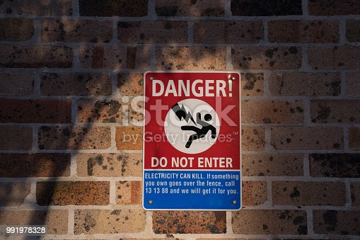 istock Danger, do not enter sign and symbol on brick wall 991978328
