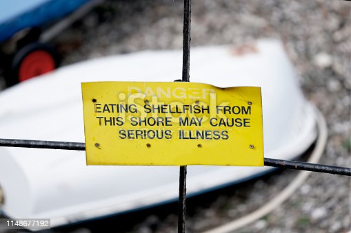 Danger eating shellfish may cause serious illness warning sign at beach uk