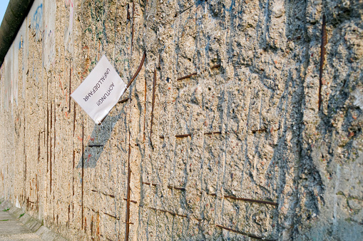 Format-filling view of the Berlin Wall (1961-1989), which was chopped off by the so-called Wall Woodpeckers, except for the Moniereisen. Inscription on a dangerously protruding Moniereisen with the German words: Warning, risk of acciden