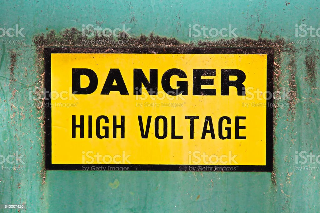 A danger high voltage sign on a green background stock photo