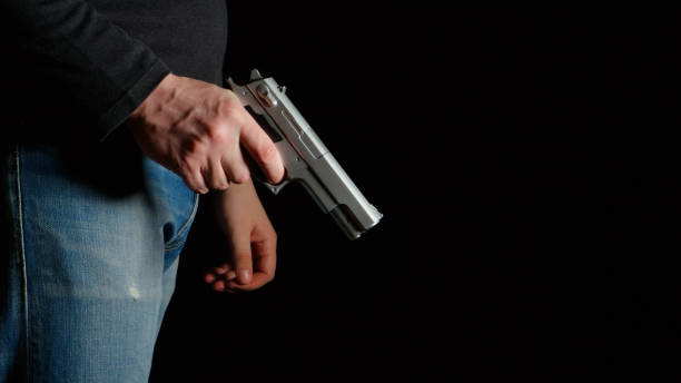 Danger man with a pistol in a dark room stock photo