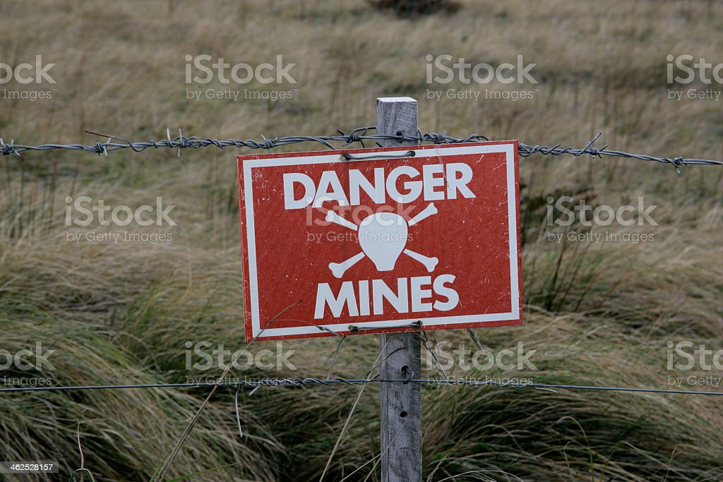 A Danger Mines sign on a barb wire fence stock photo