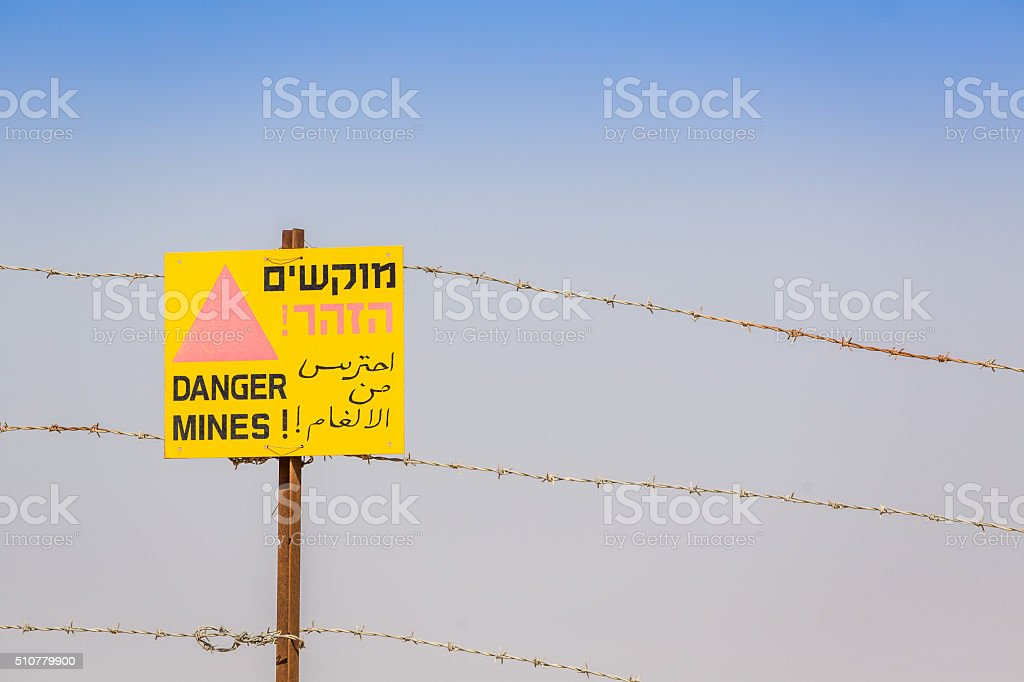 Danger Mines! Warning sign and barbed wire. stock photo