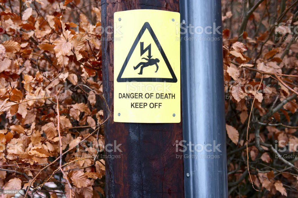 Danger of death keep off caution warning live electricity yellow sign post people risk of being killed stock photo