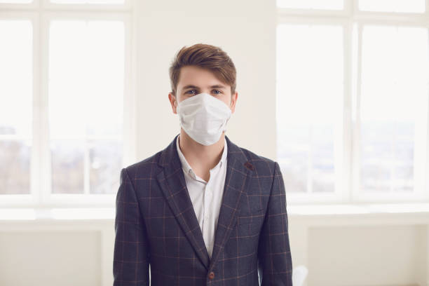 Danger of infection of the virus coronavirus infection. Businessman in medical mask at office stock photo