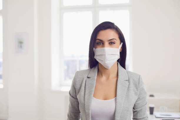 Danger of infection of the virus coronavirus infection. Businesswoman in medical mask at office stock photo
