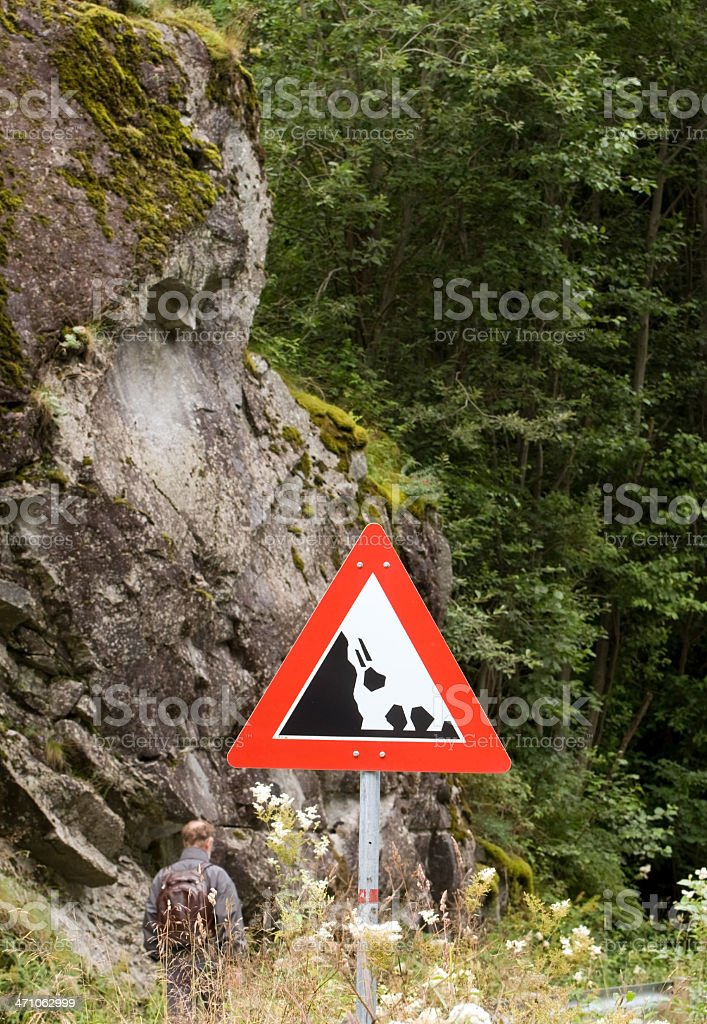 \'Falling rock\' warning sign. Man walking on the road.