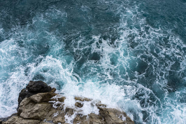 Danger sea wave crashing on rock coast with spray and foam before storm in Autum Positano, Italy stock photo