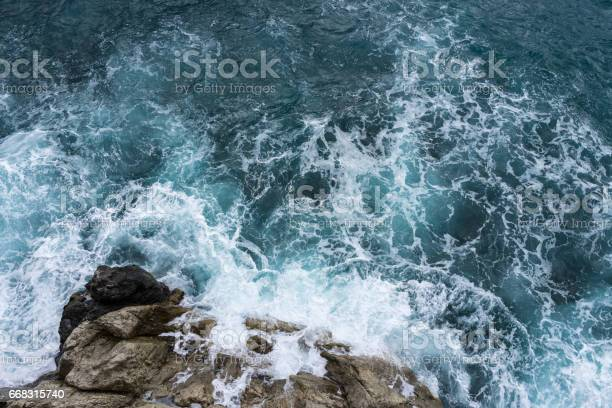 Photo of Danger sea wave crashing on rock coast with spray and foam before storm in Autum Positano, Italy