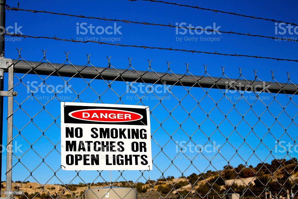 Danger sign, chain link and barbed wire stock photo