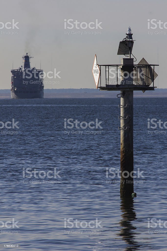 Danger Sign on Piling - Navy Ship in Distance royalty-free stock photo