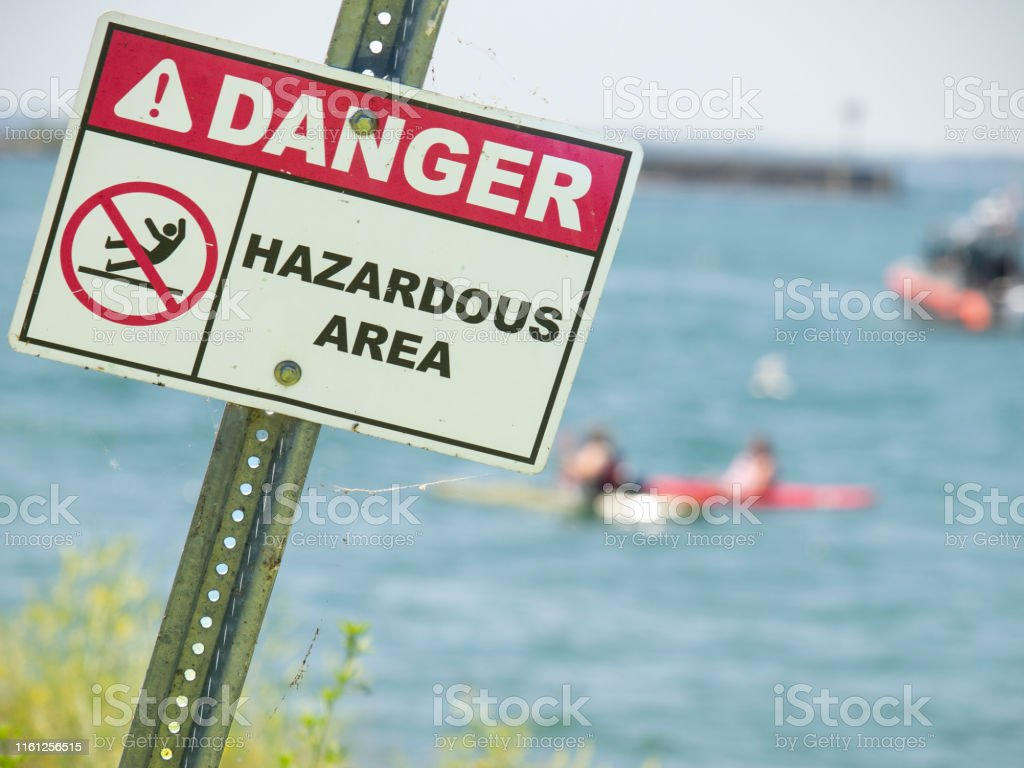 Warning sign that says Danger Hazardous Area with kayakers seen on...
