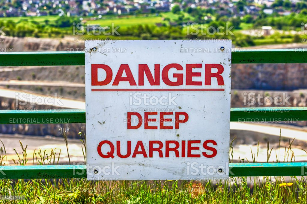 Danger sign placed at the edge of an open Quarry in rural Somerset UK stock photo