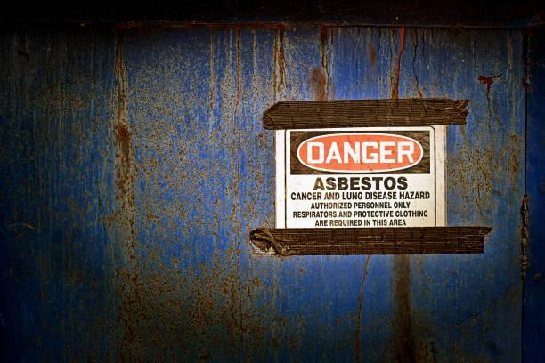 Danger sign warning of possible asbestos content beyond door stock photo