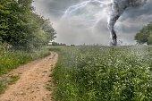 Danger storm producing a Tornado over green field