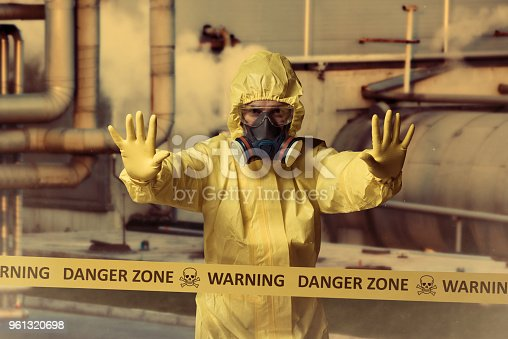 Man wearing protective suit standing behind cordon tape