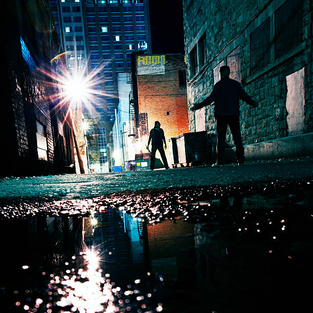 dangerous alley two dark figures face off on dark alley. alley stock pictures, royalty-free photos & images