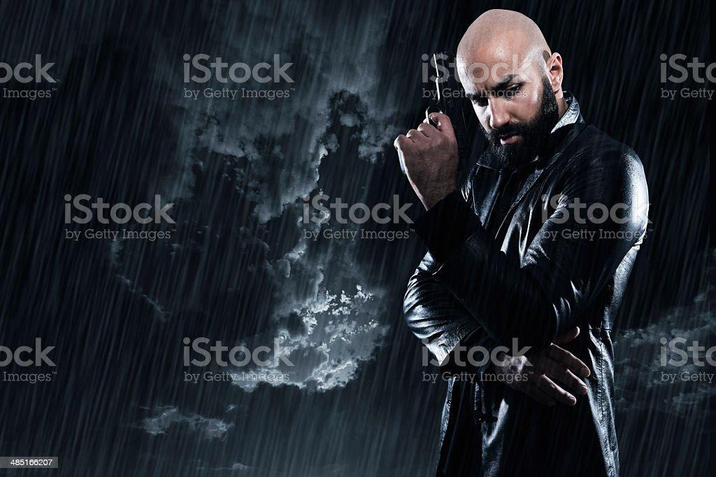 Dangerous bald gangster man with beard holding gun. stock photo
