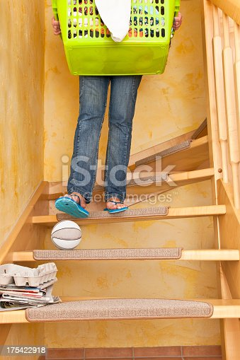 Woman carrying a basket of laundry down the stairs and overlooks a ball lying on the stairs. Accident and Insurance Themes. Risk of home accidents caused by a ball on the stairs, such an accident can be fatal. Dont be careless never use stairs as a shelf.