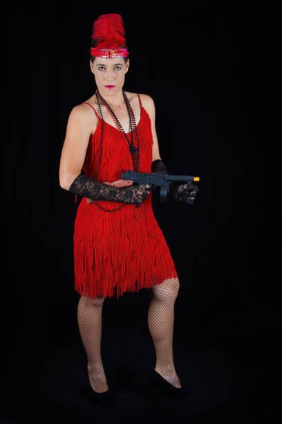 gefährlich schöne brünette in 1920 stil kleidung rot zu kleiden, feder und eine pistole - die wilden 20er stock-fotos und bilder