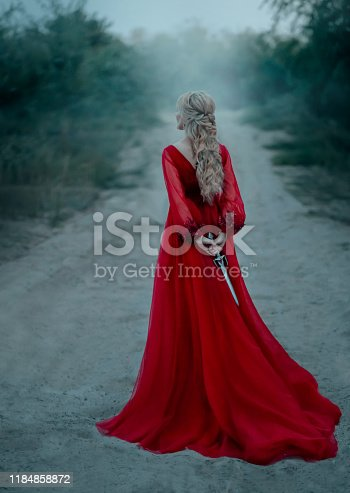 dangerous blonde queen in red fashion lush dress Hides a dagger behind. Backdrop dark fantasy forest in fog. Concept Revenge conspiracy betrayal. Halloween party. Turned away without face. Long train