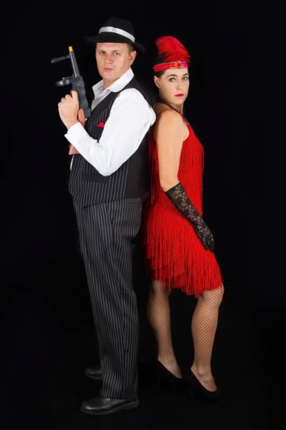 gefährliche bonny und clyde gangster mit 1920 stil kleidung stehend mit einer pistole - die wilden 20er stock-fotos und bilder