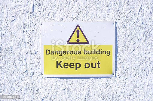istock Dangerous building keep out warning caution sign on white wall at construction building site 941563226