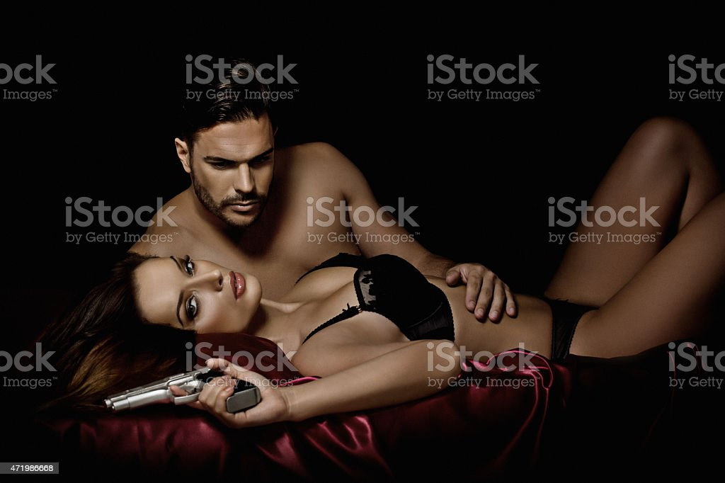 dangerous couple laying down in bed stock photo