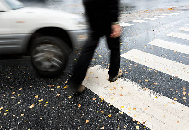dangerous crossing Man on pedestrian crossing in autumn, in danger of being hit by car misfortune stock pictures, royalty-free photos & images